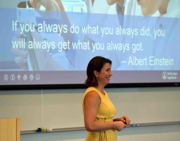 "Monica Figuerido speaking in front of Albert Einstein quote: ""If you always do what you always did, you will always get what you always got."""